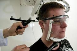 Repérage de points anatomiques de référence sur la tête d'un sujet, en préparation d'une séance robotisée de stimulation magnétique transcrânienne (TMS). Il s'agit de réaliser une séance d'essai du robot prototype. Afin de mettre en correspondance la tête du sujet avec les images de son cerveau issues d'une IRM, un manipulateur repère à l'aide d'un stylet l'oreille droite du sujet. Le sujet porte des lunettes munies de capteurs permettant à une caméra de mesurer sa position en temps réel. La TMS est utilisée en psychiatrie, dans le traitement de la dépression ou de la schizophrénie. Elle consiste à stimuler des zones du cerveau par des impulsions magnétiques indolores, avec une sonde appliquée sur le cuir chevelu.